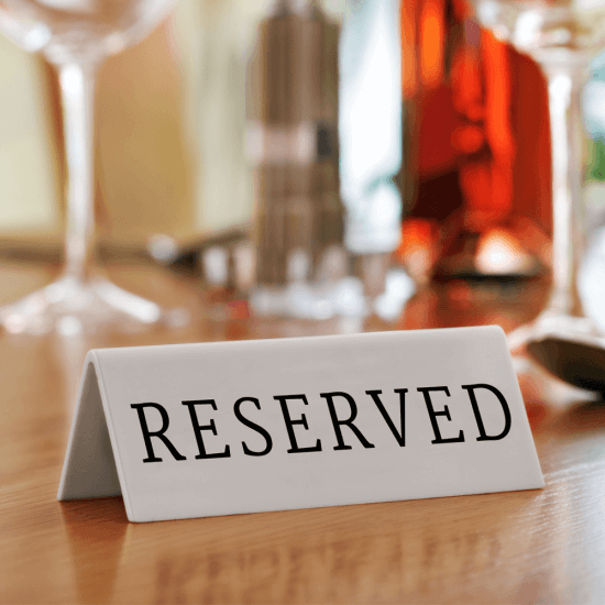 Each reserved table sign is made from white acrylic with black print