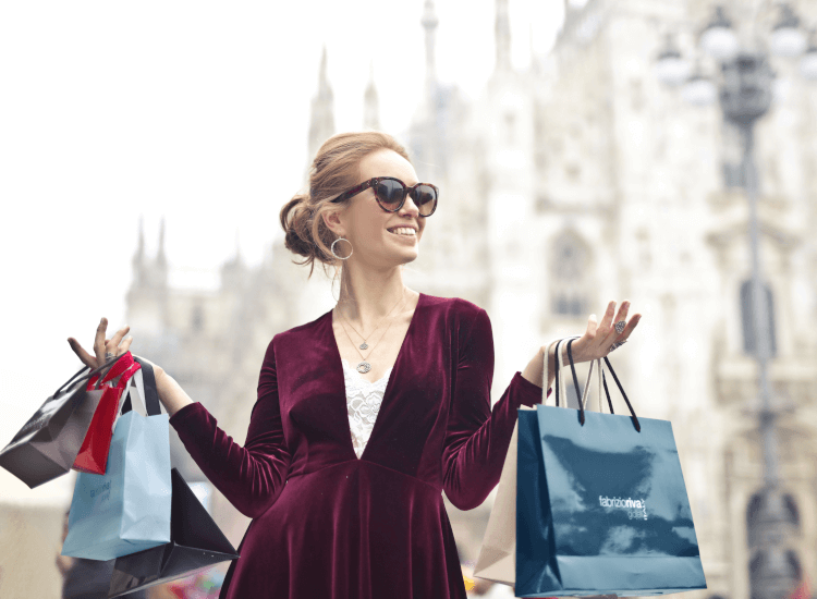 Woman gleefully carrying branded shopping bags