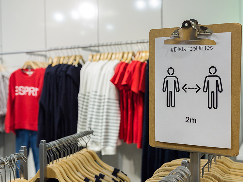 A social distancing sign at a fashion retail store