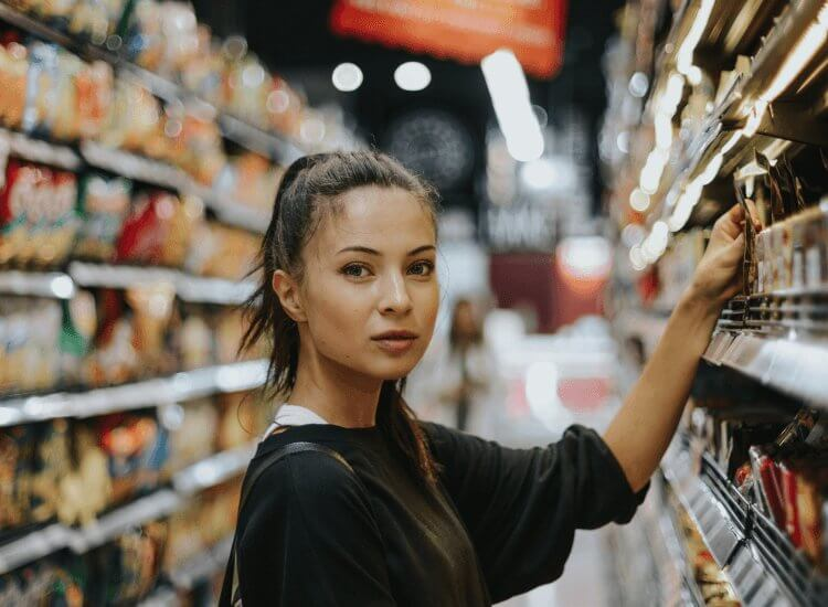 Image shows woman selecting a product from supermarket shelving