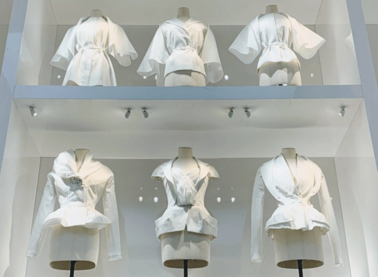 Museological garment display with designer clothes in glass cabinet