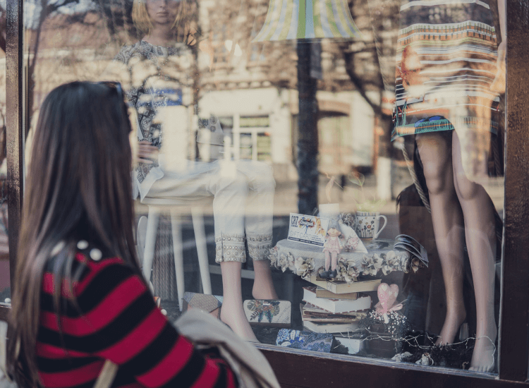 Person gazing at mannequins in a shop window